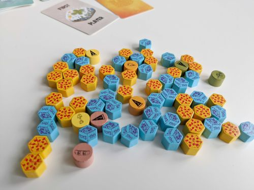 An array of wooden hex-shaped tokens including blue toy boxes and yellow pizzas